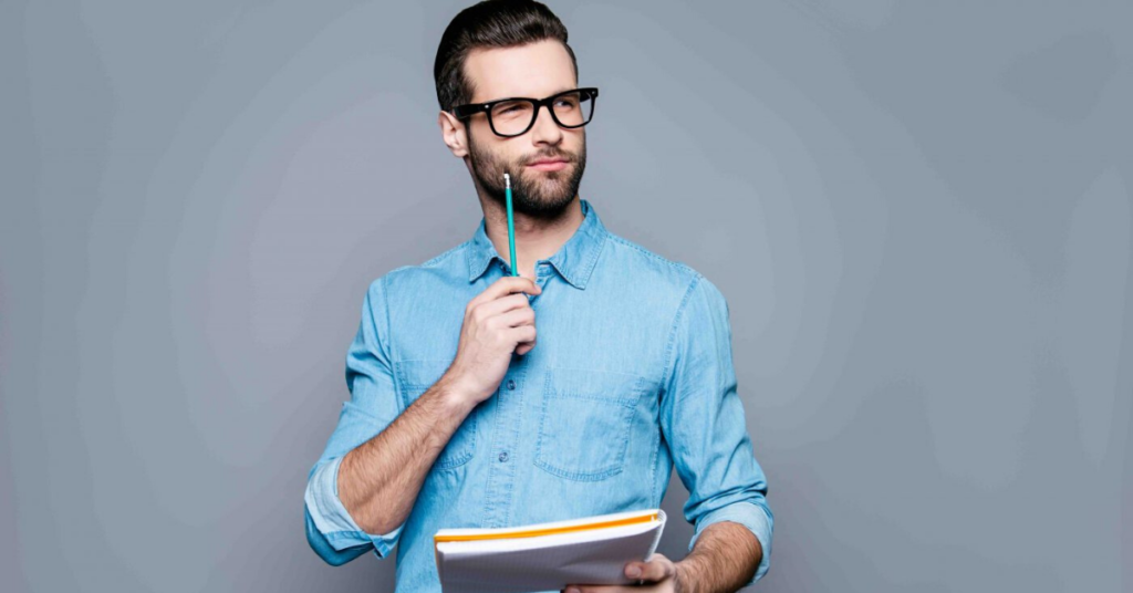 A young man wearing spectacles and holding pen and notebook, thinking to do things during coronavirus quarantine period
