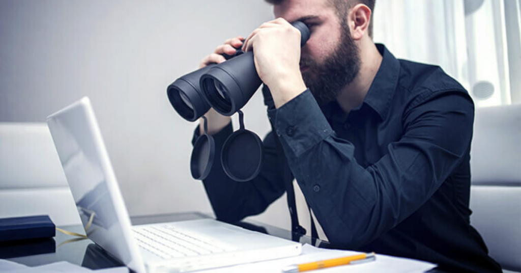 A student looking for IELTS Classes in Ludhiana on Laptop using a Binoculars